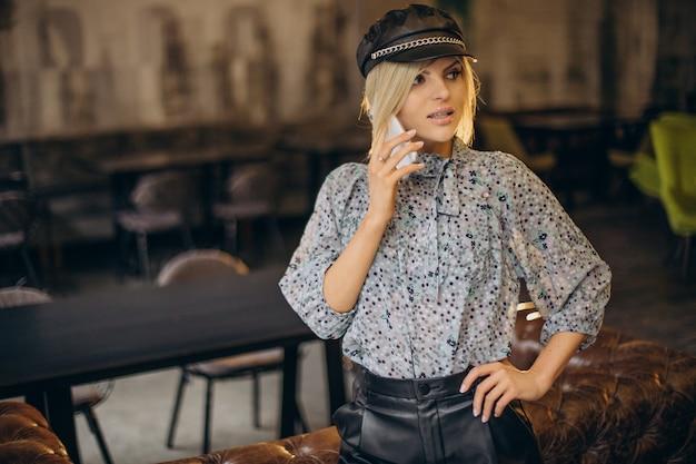 Женщина моды в кафе разговаривает по телефону