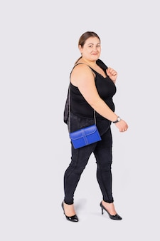회색 배경에 격리된 오른팔에 파란색 가방을 들고 검은 청바지와 셔츠를 입은 좋은 분위기의 패션 여성