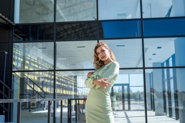 Женщина моды в зеленом платье возле стеклянного современного здания. стильный женский портрет