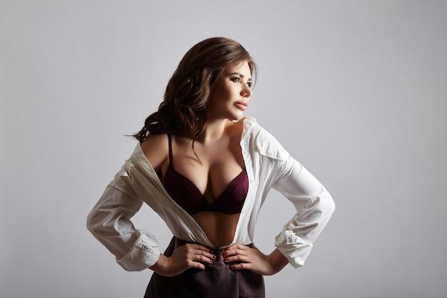Женщина моды в нижнем белье и белой рубашке с открытой грудью и короткой юбкой. сексуальная девушка позирует