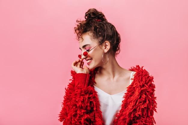 분홍색 배경에 웃 고 빨간 옷에서 패션 여자