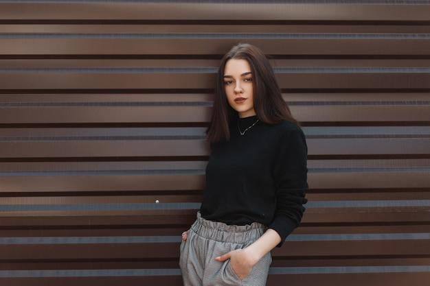 Модная женщина в стильной одежде возле металлической стены