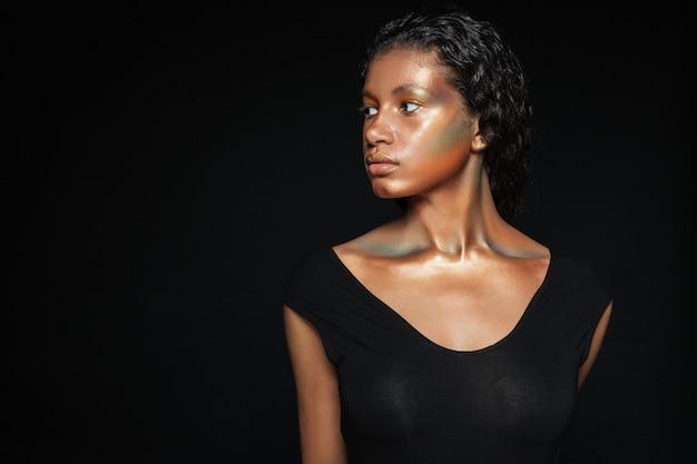 目をそらしているスタジオでtシャツを着たファッションの女性。