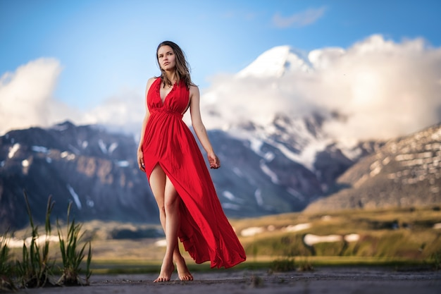 Fashion woman in a long red dress in majestic mountains.