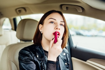 Fashion woman making up her lips with red lipstick in car