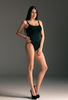ファッションの女性の肖像画。黒の水着で美しい十代のモデル。