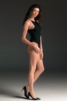 ファッションの女性の肖像画。黒い水着の美しい若いモデル。スタジオ撮影、灰色の背景。