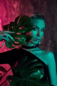 열 대 단풍 네온 불빛에 패션 여자 초상화입니다. 젖은 머리카락, 완벽한 몸매 및 메이크업. 핑크와 그린 네온 컬러