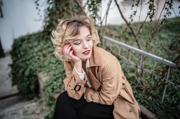 ヨーロッパの街でポーズをとる若いかなりトレンディな女の子のファッション女性の肖像画、春のストリートファッション。笑って、笑顔の肖像画。レトロなスタイル、レインコートと赤い唇