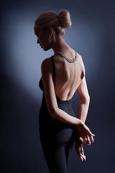暗い背景の上のファッションの女性の肖像画、美しい曲がった背中を持つシルエットの女性。