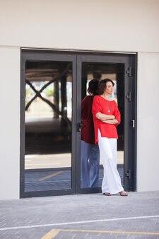 Портрет женщины моды представляя в городе. портрет красивой деловой женщины. женщина, стоящая возле стеклянной двери