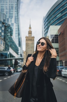 Fashion woman portrait of young pretty trendy girl posing at the city in europe.