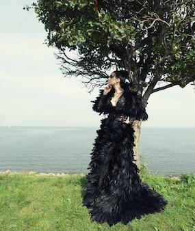 Женщина моды позирует на берегу моря. темная королева.