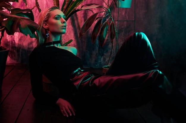 열 대 단풍 네온 빛에 바닥에 앉아 패션 여자. 젖은 머리카락, 완벽한 몸매 및 메이크업. 핑크와 그린 네온 컬러
