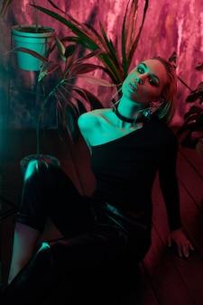 熱帯群葉ネオンの光で床に座ってファッション女性。濡れた髪、完璧な姿とメイク