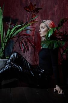 熱帯紅葉ピンクの光の中で床に座ってファッション女性。濡れた髪、完璧な姿とメイク