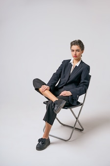 Fashion woman sitting in a suit on a chair on a white background, bright makeup and short hair