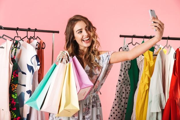 Модная женщина делает селфи на смартфоне в магазине возле вешалки с красочными сумками, изолированными на розовом