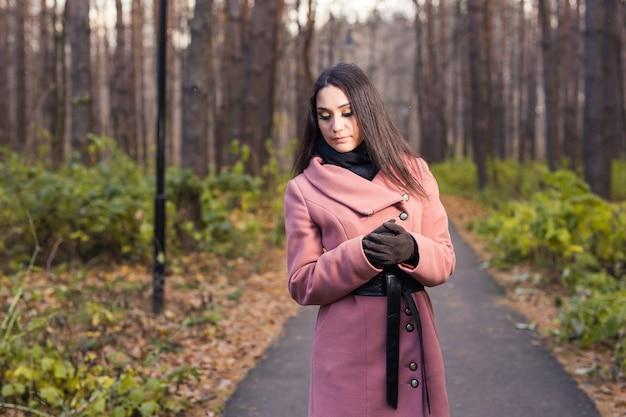 秋の公園を歩くファッションの女性