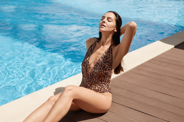 Fashion woman wearing leopard printed bikini with perfect tanned skin, attractive lady sitting near swimming pool, young female spending summer time on luxury resort. relaxing concept.