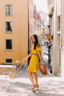 여름 드레스와 선글라스를 착용한 패션 여성이 야외에서 거리를 걷습니다.