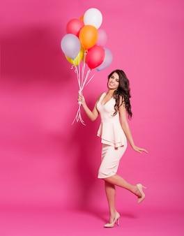 Женщина моды с воздушными шарами на розовом