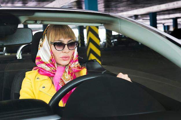 ブロンドの髪とセクシーなスタイルの運転スポーツカーを持つファッションの女性。黄色いジャケットとカブリオレのハンカチの若い金持ちの女の子。