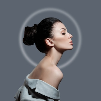 Fashion woman with a bunch of hair in light circle. perfect face profile girl, natural cosmetics for face care