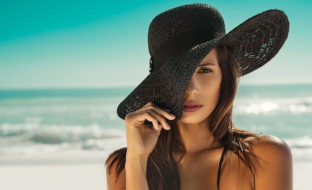 ビーチで麦わら帽子のファッション女性