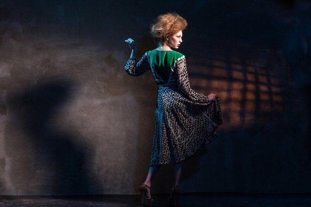 어둠 위에 녹색 드레스를 입은 패션 여성