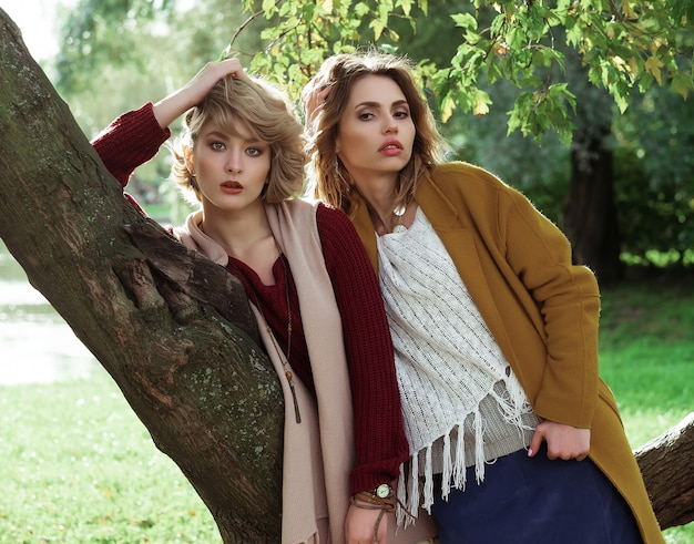 Fashion women posing together outdoor, autumn park.