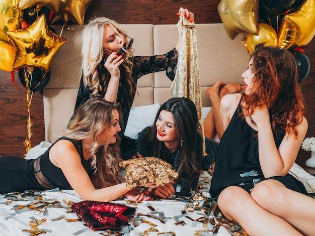 ファッション女性のリラクゼーション。スパンコールの衣装を選択してベッドに横たわっている黒の若い女性。お祝いの紙吹雪と風船の装飾。