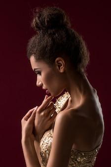 Молодая африканская женщина моды с косметикой в сексуальном золотом платье
