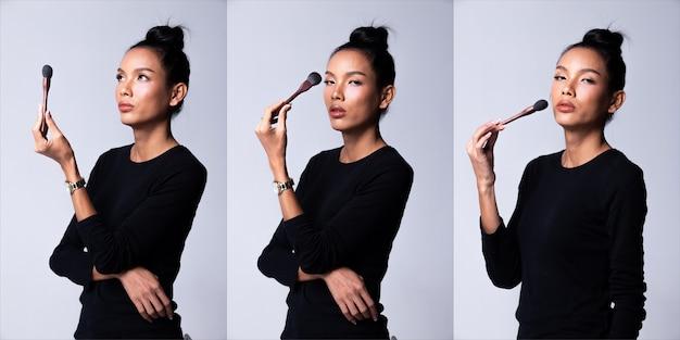 패션 젊은 아시아 트랜스젠더 여성 얇은 검은 머리가 아름다운 패션 검은색 긴 소매 드레스를 입고 포즈를 취하고 브러시를 메이크업 아티스트로 잡고 있습니다. 스튜디오 조명 흰색 배경, 콜라주 그룹 팩