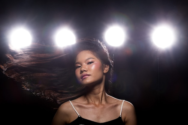 Fashion young asian woman tan skin black hair eyes beautiful make up fashion dress. studio lighting dark background smoke fog back rim light low exposure