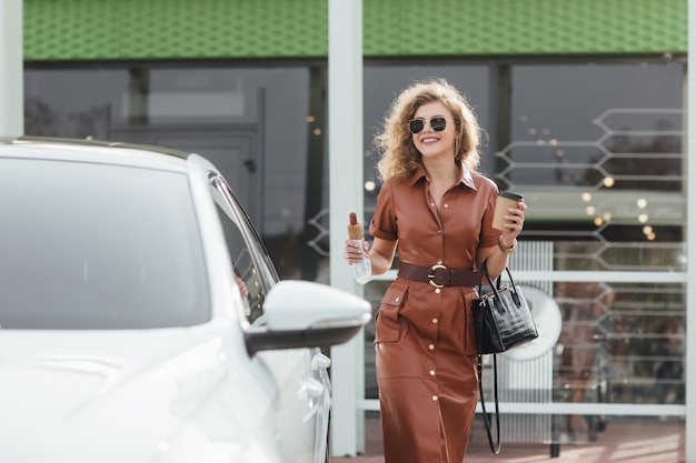 ガソリンスタンドの車の近くの駐車場でホットドッグを食べるファッション若いブロンドの女性