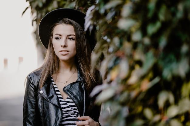 ファッション若い茶色の髪の少女の革のジャケット、街の遊歩道の黒い帽子