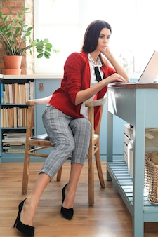 Fashion young brunette woman working from home with laptop. teleworking concept