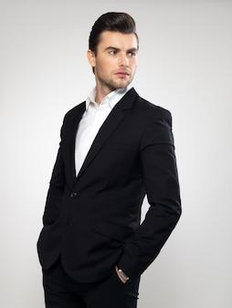 Moda giovane uomo d'affari vestito nero posa casual in studio
