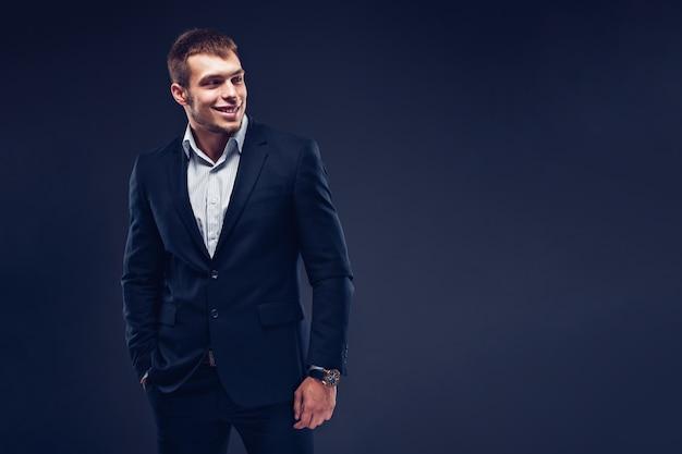 Fashion young businessman black suit on dark background