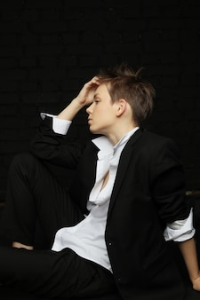 Fashion young cute girl with light short hair in men suit on dark background