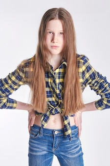 Fashion young girl in shirt and jeans posing on a white wall. model school for children.