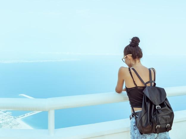 山からの眺めを楽しむカジュアルな服のメガネのバックパックを持つファッションの若い女の子