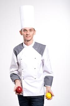패션 젊은 남성 요리사 요리사 또는 베이커 남자 흰 벽 배경 스튜디오 초상화에 고립 된 흰색 유니폼 셔츠 포즈에. 요리 음식 개념. 복사 공간을 모의합니다. 사과와 레몬을 들고