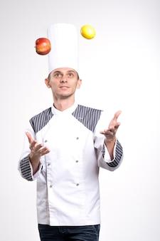 패션 젊은 남성 요리사 요리사 또는 베이커 남자 흰 벽 배경 스튜디오 초상화에 고립 된 흰색 유니폼 셔츠 포즈에. 요리 음식 개념. 복사 공간을 모의합니다. 저 글스 사과와 레몬