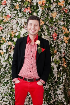 Fashion young man in black suit and red pants casual on background floral decor wall.