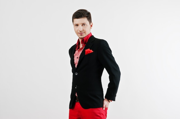 Fashion young man in black suit and red pants casual poses