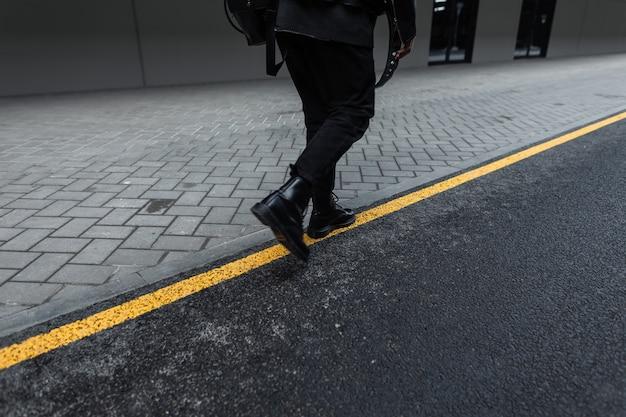 トレンディな黒のバックパックと革のファッショナブルなブーツでヴィンテージジーンズのスタイリッシュなジャケットを着たファッションの若い男は、屋外の通りを歩きます。ユースブラックウェアのクールな男。背面図。黄色い線