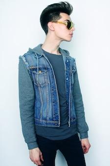 白い背景の上のファッショナブルなサングラスとファッションの若い男