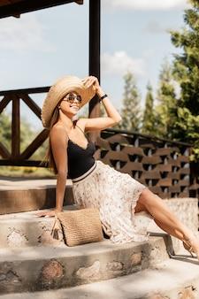 スカートとヴィンテージのランジェリーで編まれたハンドバッグと麦わら帽子のサングラスとファッションの若いモデルの女性は、階段に座って自然の中で休んでいます